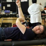 Holding gauze to her arm, senior Amber Bailey finishes up giving blood.