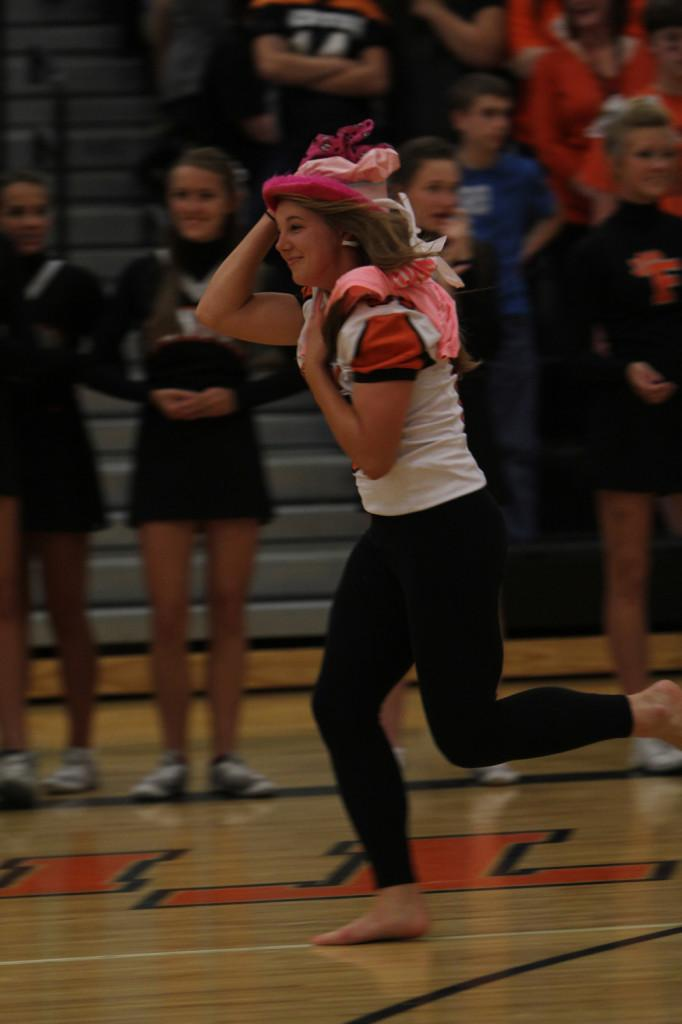 Senior Kayla Stiles sprints across the gym during a relay race at the Homecoming pep rally.