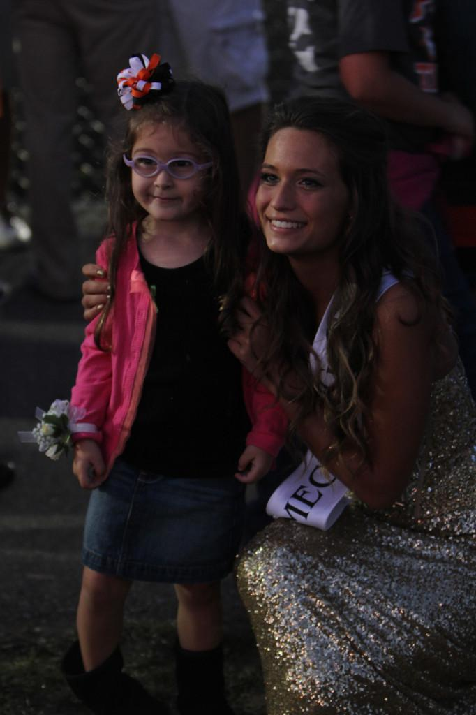 Homecoming Queen, Sarah Hamilton, poses for a picture with a young girl during the game.