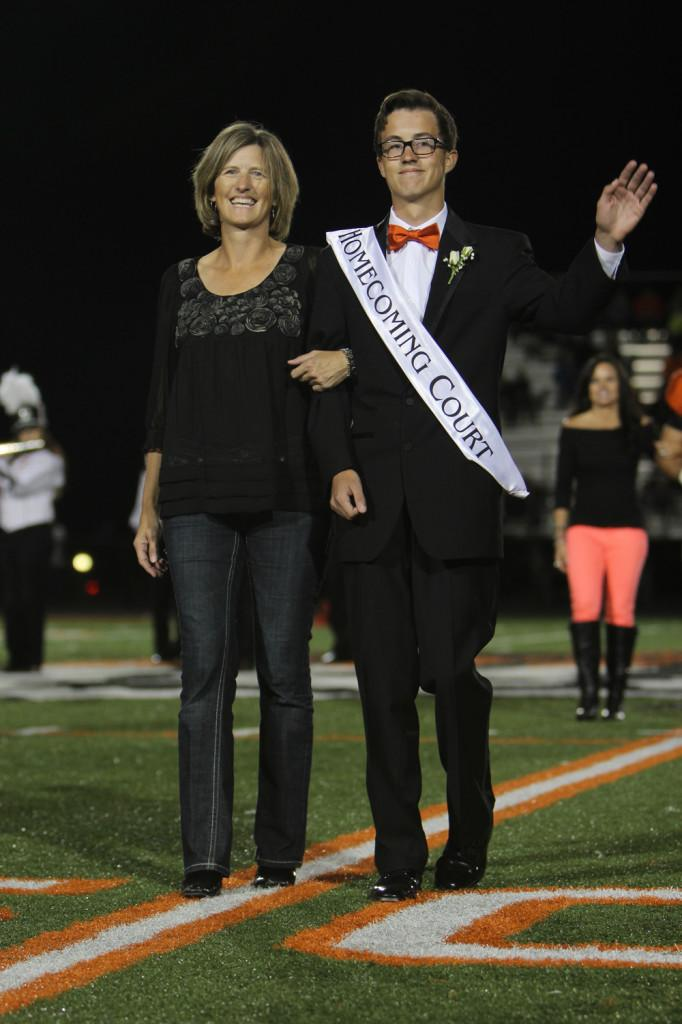 Senior Jack Pooler waves to the crowd as he is introduced as a member of the Homecoming court. He is escorted by his mother.