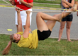 Hanging upside down, junior Julia Johnson crawls across a rope at the Hero Dash. The Hero Dash features challenges like moving hay bales, completing pushups, crawling under barbed wire and finding a superhero cape.
