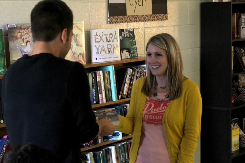 English teacher Sarah Andersen hands senior Landon Mikulenas a new book to start reading during her classes' sustained silent reading.