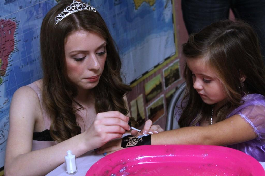 NHS member Lauren Rumbles dresses up like a princess and paints a little girl's nails at the Princess Ball fundraiser