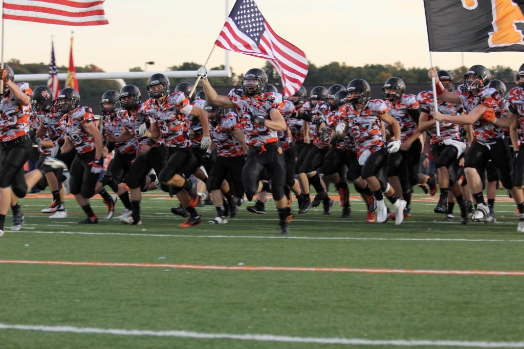 The Tigers storm the field before kick off at the Wounded Warrior Game