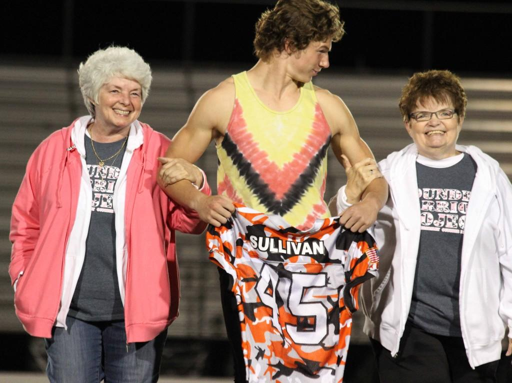 Junior Cameron Covacs walks the women who's relative he honored down the football field after the Wounded Warrior Game