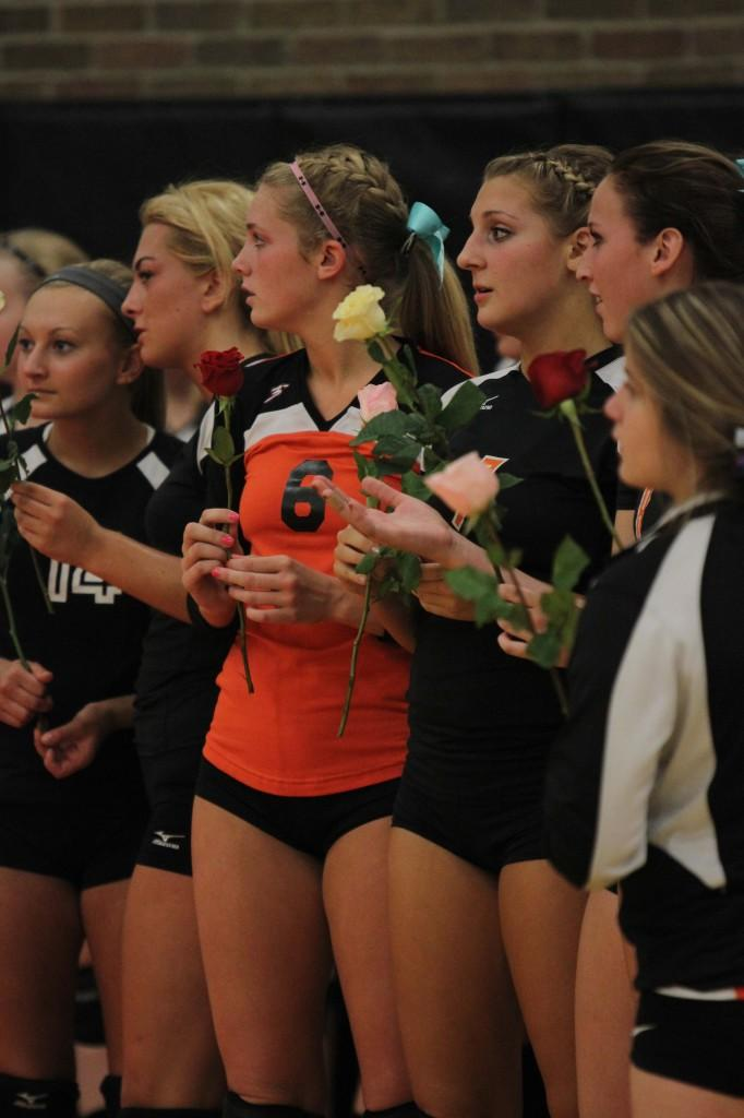 The varsity volleyball players stand on the sideline holding roses to honor their senior players on senior night.