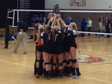 The Fenton Varsity Volleyball team celebrates their second straight district title win.