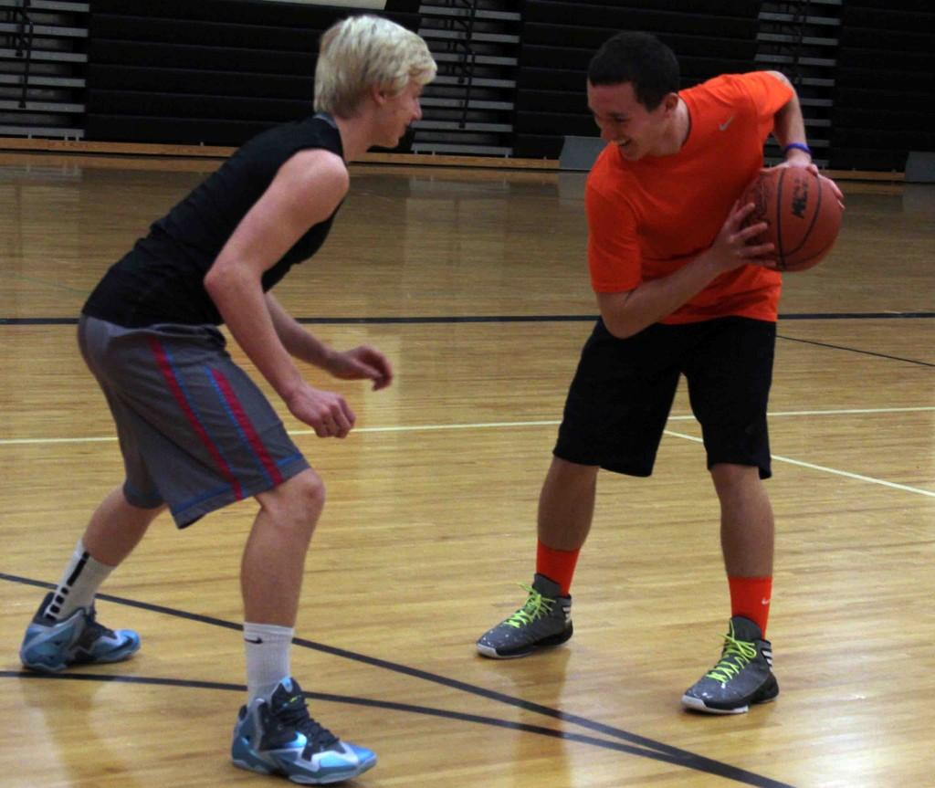 Getting in a game of basketball after school, junior Beau LePage attempts to keep the ball away from junior Dillion Gardner. LePage and Gardner often practiced after school during the off season with other teammates to prepare for the regular season.
