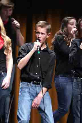 """Belting it out. Sophomore Sam Strickhouser performs during the Ambassador Sneak Preview Show on Nov. 23. The concert featured renditions of """"Some Nights"""" by Fun and """"Celebrate Me Home"""" by Kenny Loggins."""