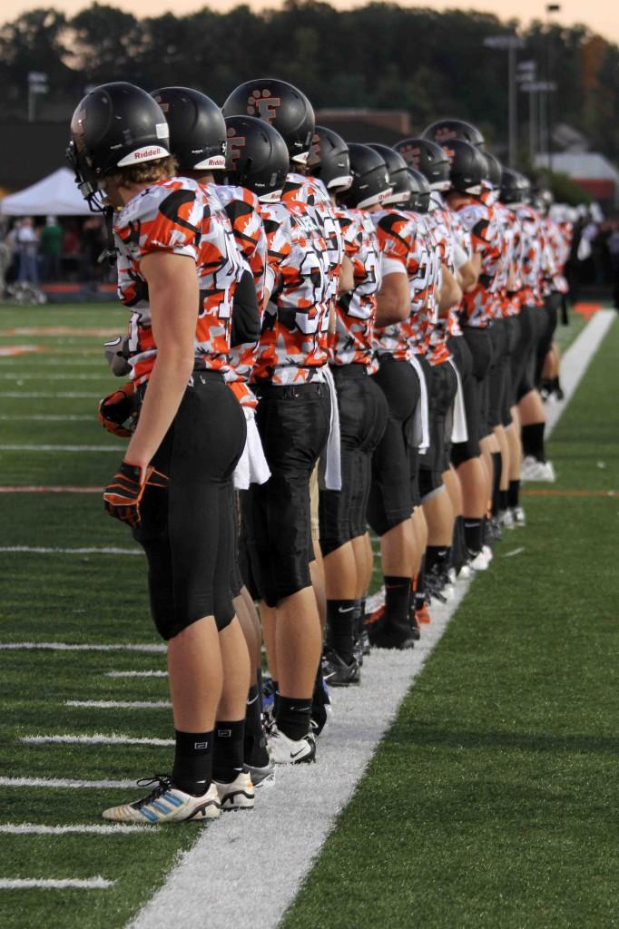 The varsity football players line up for the National Anthem before the Annual Wounded Warrior Game