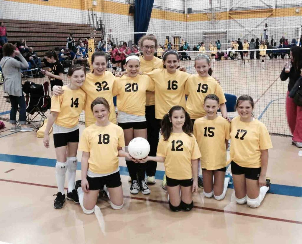 After a weekend tournament, senior Ashley Bearden poses with the volleyball team she coaches. Bearden coaches a group of 12 year old girls through the Southern Lakes Parks & Recreation volleyball program.