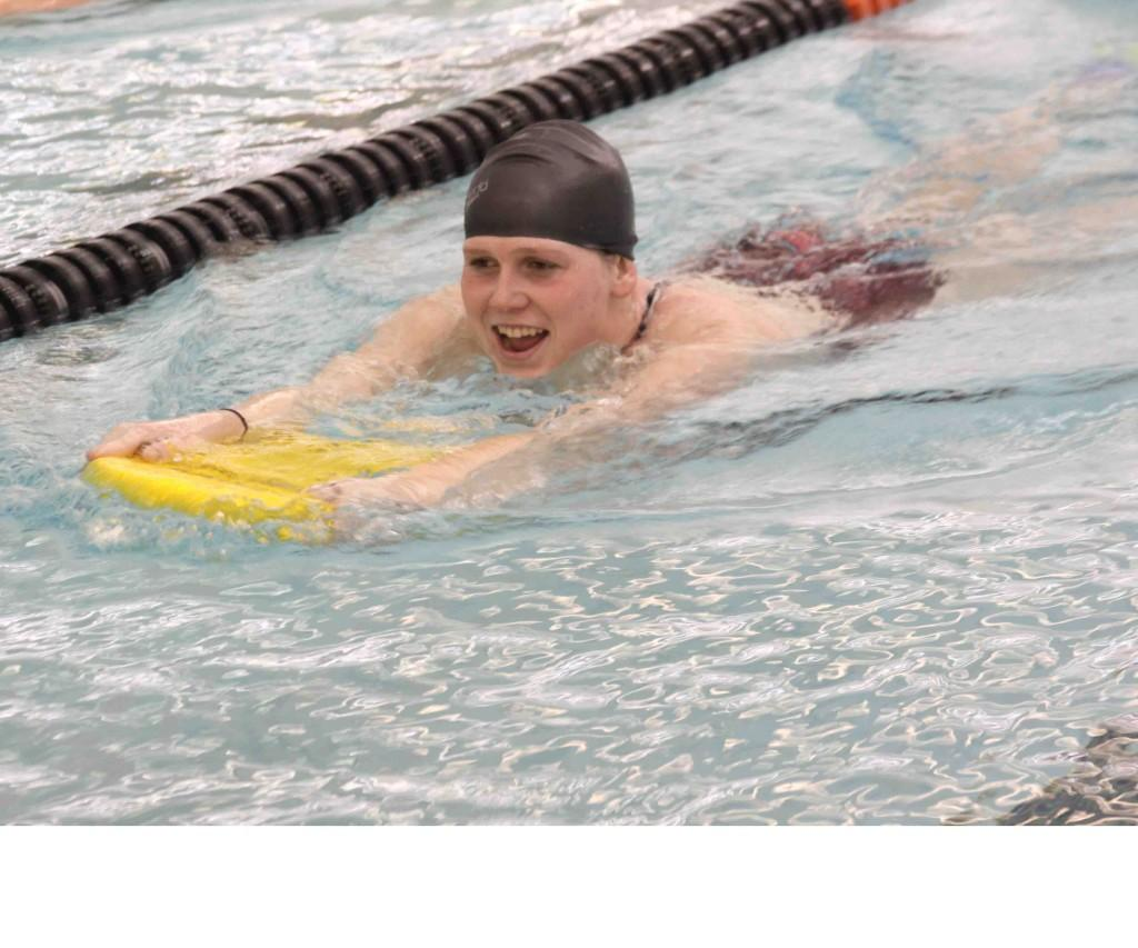 Sophomore Taylor Haaraoja demonstrates using a kick board how to properly kick when swimming. Along with Haaraoja, seniors Alexis Kontorousis and Marissa Kimmell help coach swimming as well.