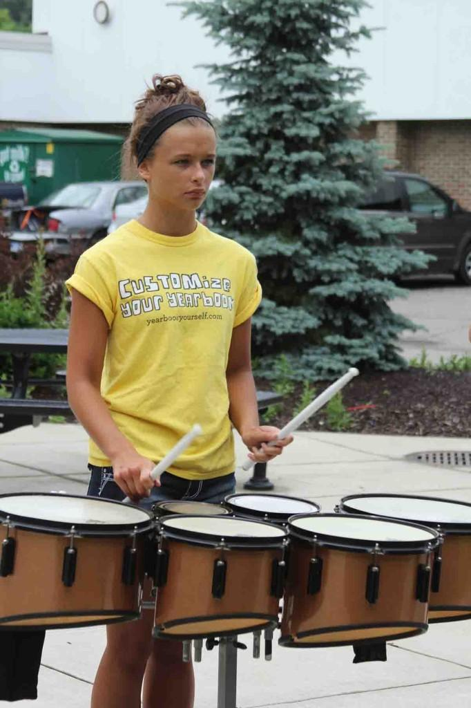 During a morning practice in the summer, sophomore Marissa Bellinger participates in a drumming drill with her fellow drumline members.  Many members of the summer drumline also participate in Winterline. The winter drumline will make their first appearance at halftime of the boys varsity basketball game on Feb. 21.