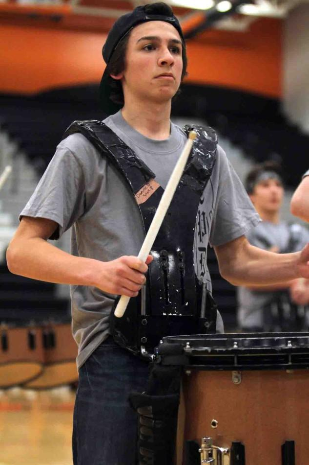 """Snare drum around his body, freshman Dom Dimambro performs at the halftime show of a basketball game on Feb 27. """"I love performing,"""" Dimambro said. """"There is something about performing and practicing as a group that brings us together. My favorite song to perform was 'Dream On' by Aerosmith."""""""