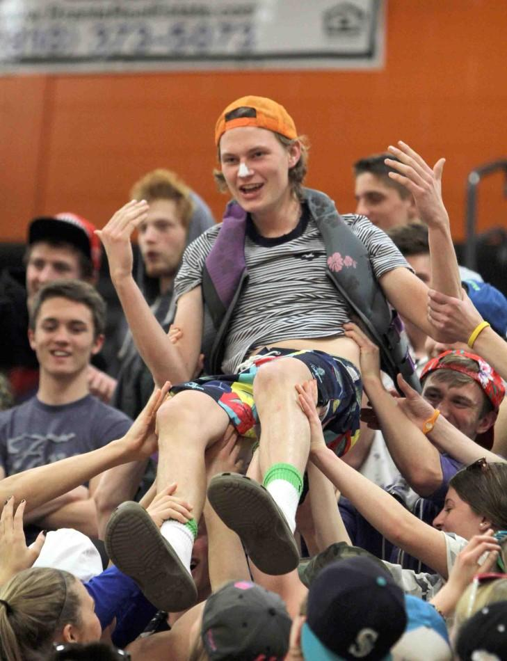 "Surfs Up. Crowd surfing through the senior side of the student section during halftime of the boys basketball game against Lapeer East on Jan. 24, senior Alex Fulton is carried upward over the crowd. ""I started crowd surfing over the seniors because we had to show up the juniors,"" Fulton said. ""The theme that night was beach night and this game was the most fun because of the huge crowd we had."""