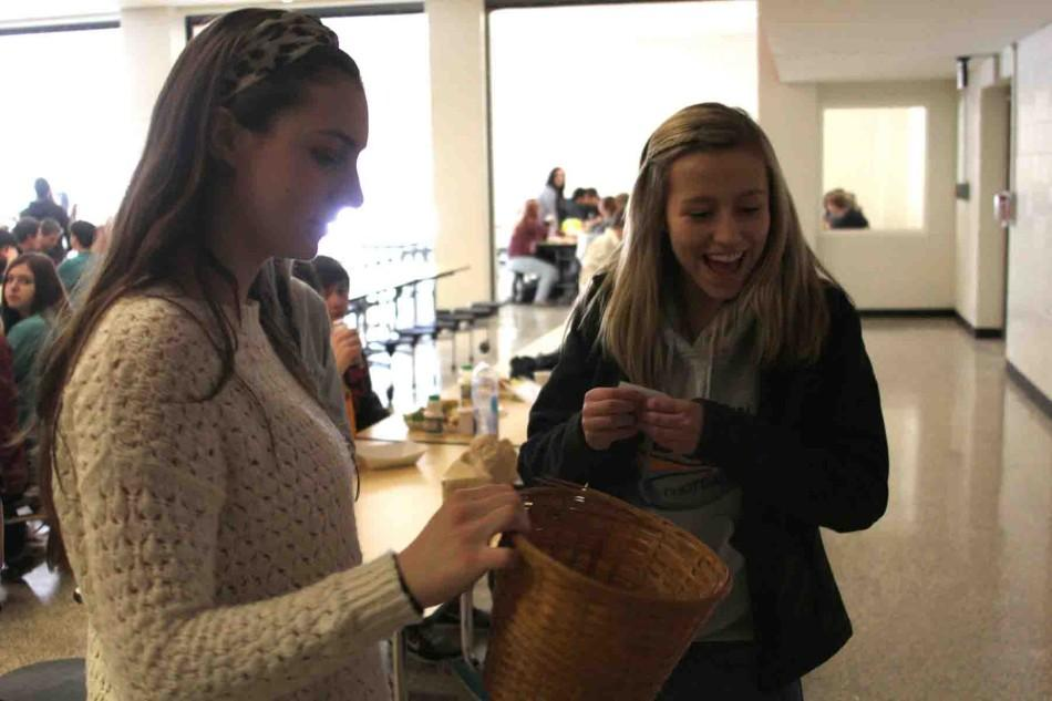 """During a game to promote yearbook sales, sophomore Alexis Brissette holds a basket for fellow sophomore Morgan Schollhammer to draw a number. """"The game was the cake walk,"""" Brissette said. """"Whoever was standing on the number drawn won a cupcake and got to be entered in our raffle."""""""