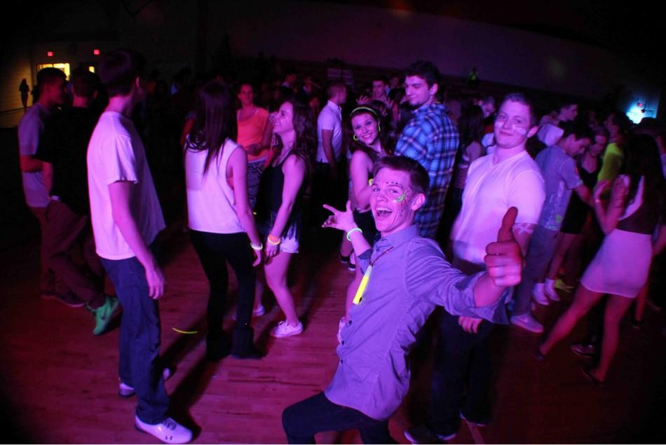"""Glowstick around his neck and face painted, senior Matt Callaghan gives a thumbs-up at the Sadie's dance. """"Everyone was actually dancing and not standing around; there was a lot of energy,"""" Callaghan said. """"It was fun to wear neon and I painted my face before the dance and got glowsticks with my friends."""""""