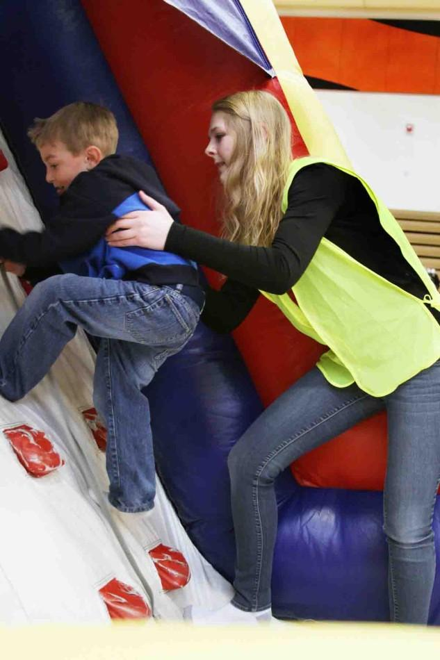 """Volunteering at the Fenton Business Expo, junior Caitlin Heenan boosts a kid up the inflatable climbing wall. """"I worked the Expo for NHS,"""" Heenan said. """"They had us work in the children play area and we helped the kids who couldn't make it up the wall. We encouraged them and told them they only had a little way to go. I enjoyed seeing the kids come back around and have a good time."""""""