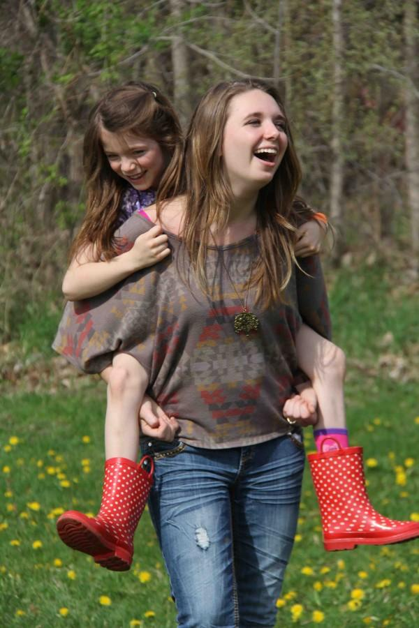 Sophomore Alex Id bonds with her 1st grade Pond Day Buddie while giving her a piggy back ride.