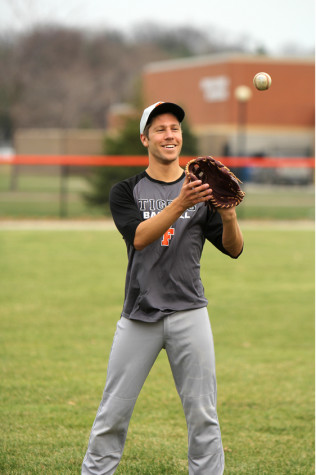Senior Landon Mikulenas plays catch during varsity baseball practice. The baseball team will face new competition from Flushing next year.