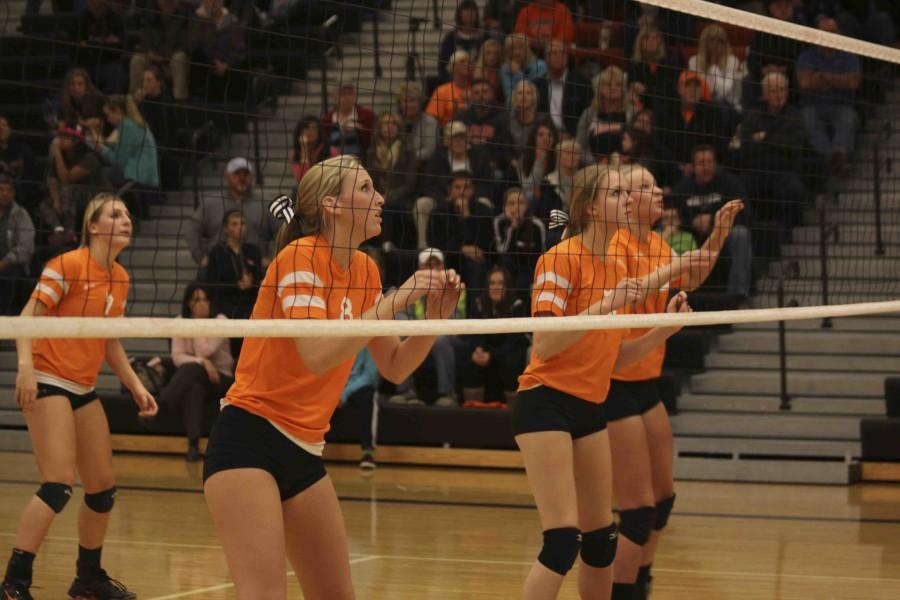 Varsity volleyball players Carly Granger, Kelsie Fischer, Jessica Warford, and Kendrah Praedel wait for the ball to be spiked in their direction.