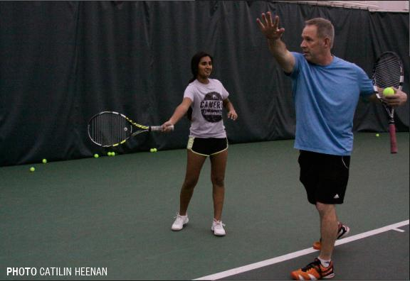 Taking a practice swing with her racket, junior Sylee Kiran perfects her forehand with advice from her coach, Gary Ballard. Kiran trains with Ballard at Genesys  twice a week for girls tennis season.