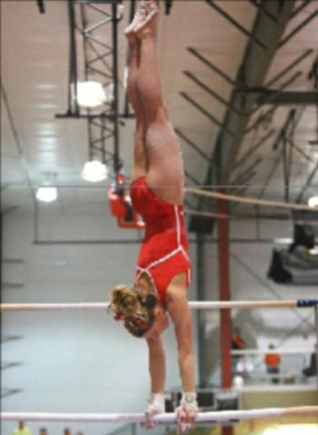 Sophomore Ashley Murphy does a handstand on uneven bars while training for her club team. She has been training for eight years.