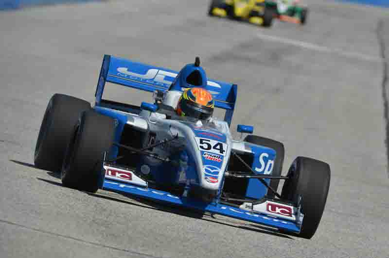 Running in 10th place at a race track in Milwaukee, Wisconsin, Mt. Morris native Michael Johnson maneuvers his car through a turn. Johnson was later eliminated from the race when he crashed his vehicle.