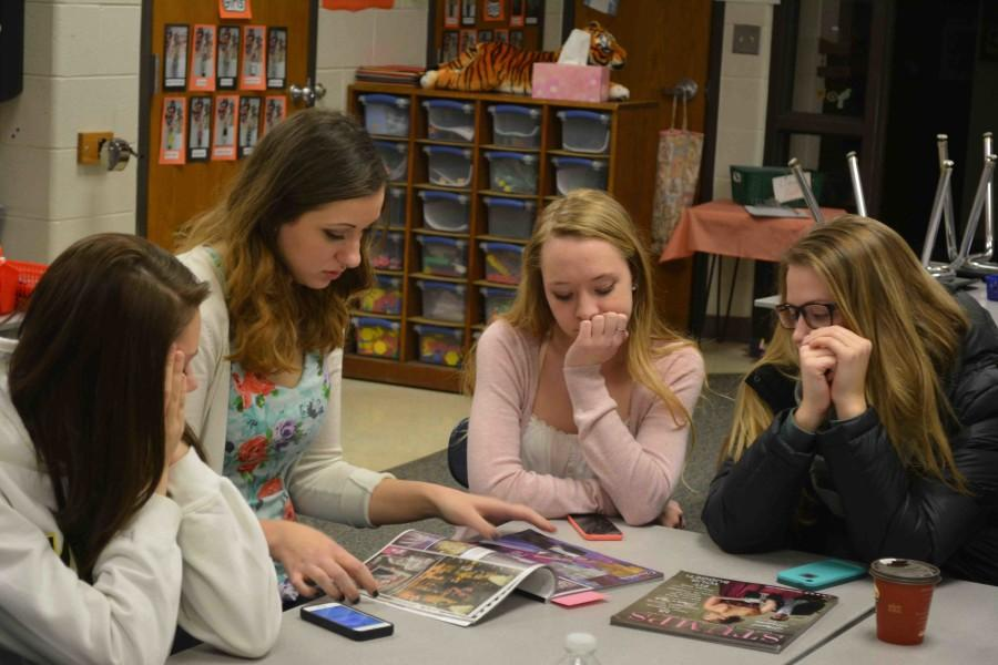 Juniors Hannah Curran, Samantha Gehm, Madison Dagenais, and Hope Dagenais look through magazines to find decorations that correspond with this year's theme,