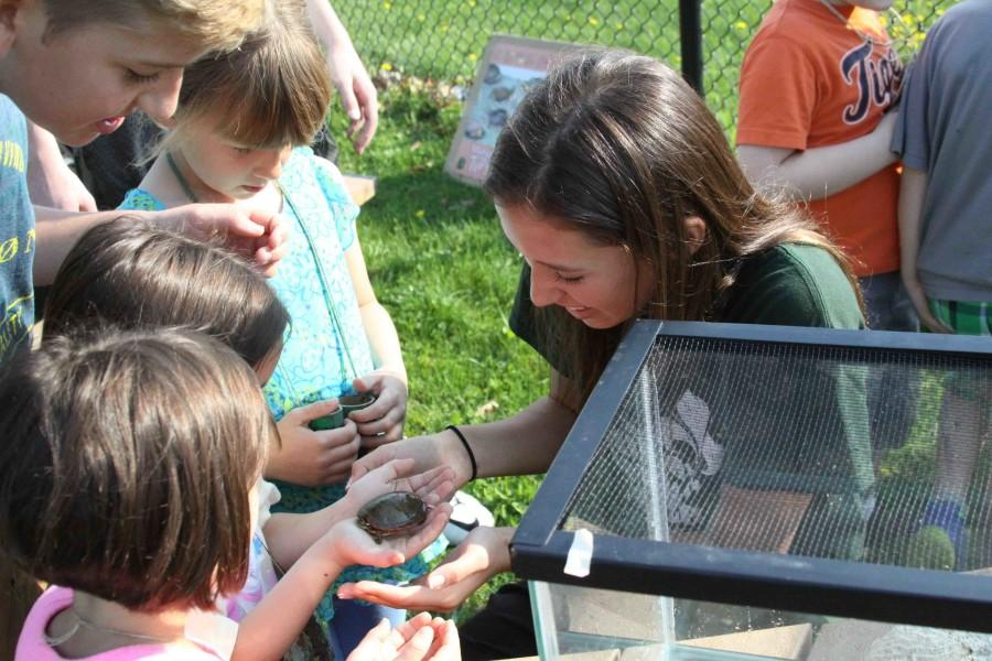 Freshman Libby Carpenter presents a turtle to the elementary school children visiting on Pond Day. Students from all three elementary schools come to learn about the natural sciences.