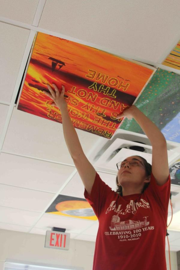 Putting her newly painted ceiling tile in the art room, senior Rosemary McWilliams and her fellow classmates leave their last piece of art for all to see.