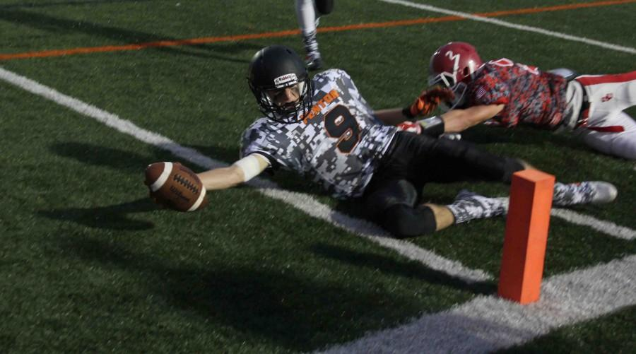 Junior Zach West reaches for a touchdown while being held back by a Swartz Creek player.