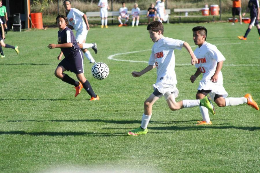 Sophomore Owen O'Brien assists sophomore  Marco Gomez to the opponents goal to score for the boys JV soccer team.