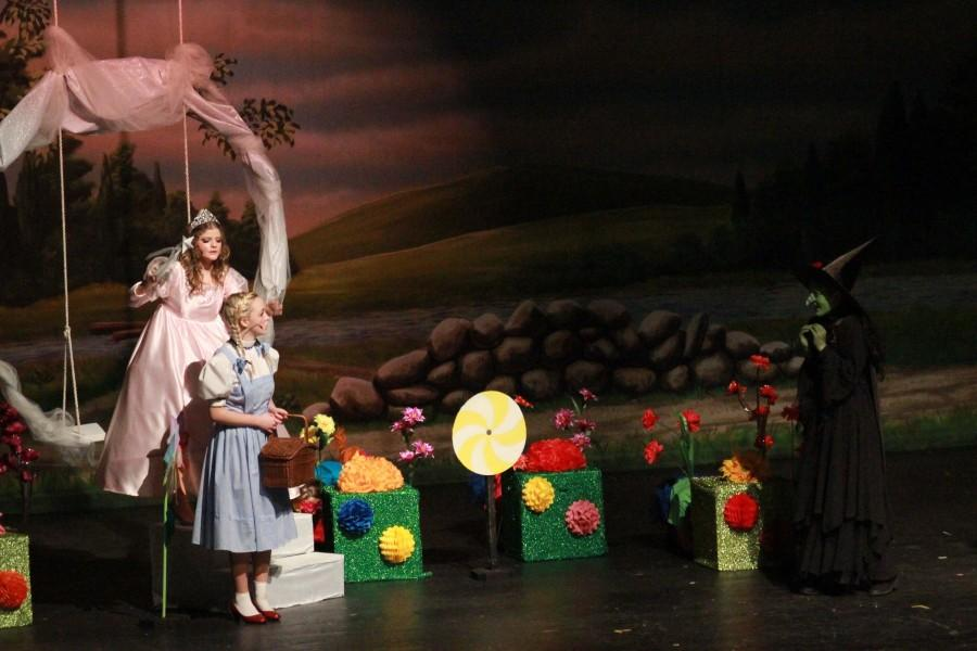 Waving her wand, Glinda the Good Witch, played by sophomore Joie Raymond protects Dorothy from the Wicked Witch to keep the peace in Munchkin Land.