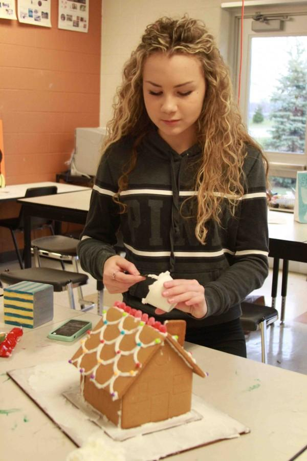 Making her gingerbread house in her sculpture class, junior Lauryn Bell adds more frosting to her creation. We were making gingerbread houses in sclupture. I bought the kit to make my house at Target and used the internet to gather information to create the gingerbread house.