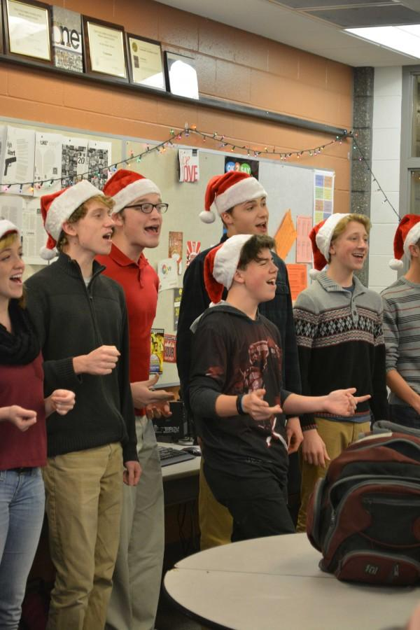 Going caroling with the Ambassadors around the school, junior Jackson Wolf sings 'Rockin' Around the Christmas Tree' with the base part.