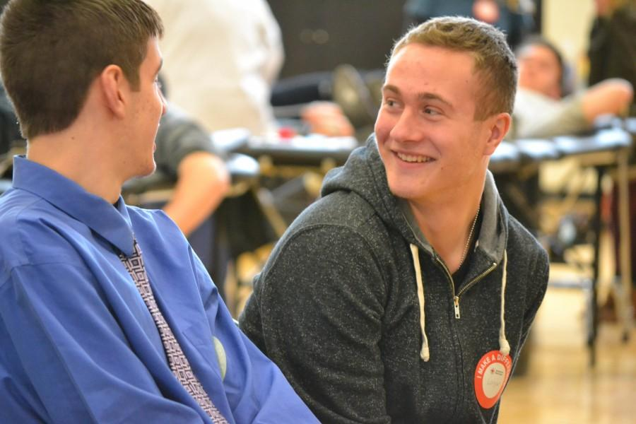 Talking to his friend at the blood drive, junior Logan Moore recovers after he gave blood.