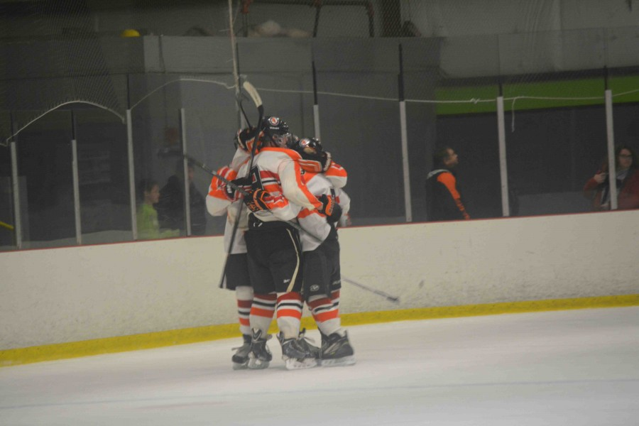 At the Griffin's hockey game vs Flushing, Clio, and Swartz Creek, junior Bobby Temple joins his team in a huddle to congratulate a scored goal.