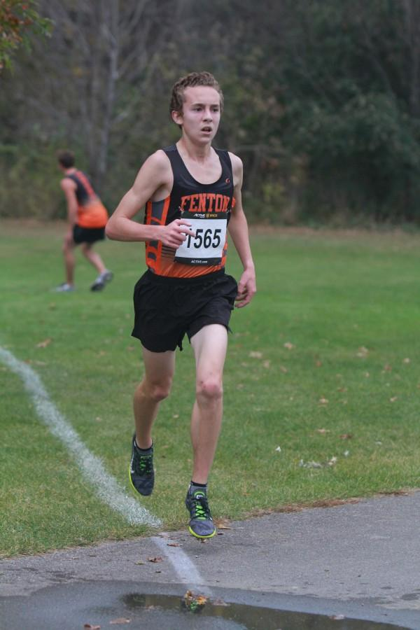 """Senior Jake Lee runs through the mud during cross country season. """"Indoor track helps us get into good running shape,"""" Lee said. """"We do similar workouts as we do during track to get our mileage up. This also helps for cross country season by keeping us in good form."""""""