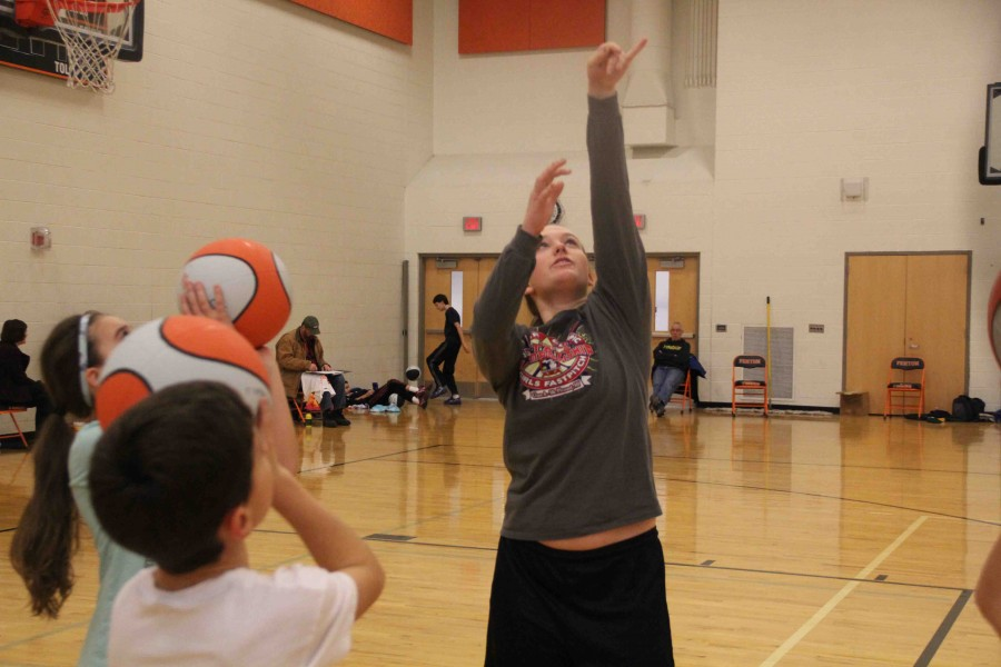 Showing the kids how to shoot a ball, junior Logan Carter helps show little kids how to play basketball at the camp.
