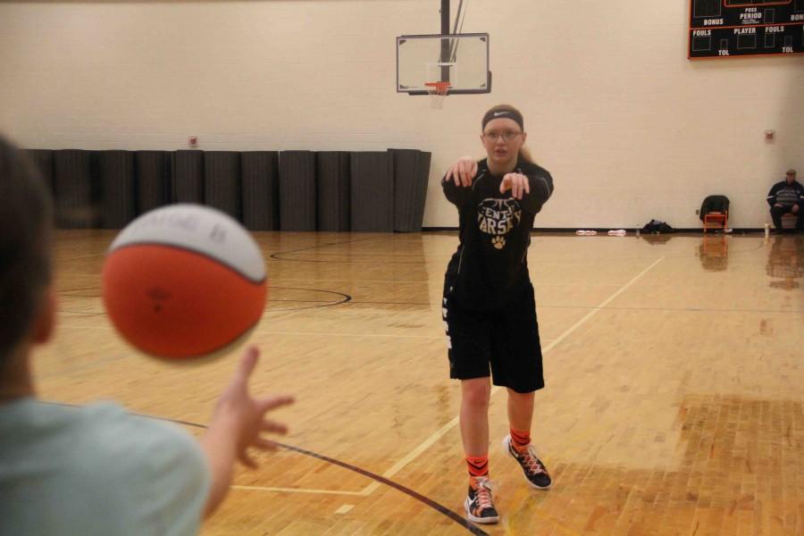 Passing a ball to a kid, senior Sarah CUmmings helps run the basketball clinic on Saturday.