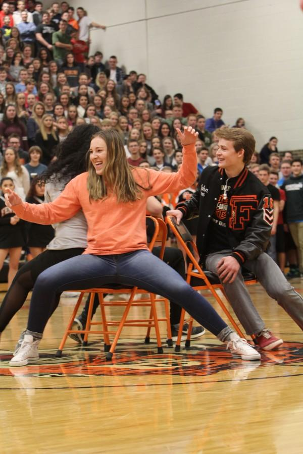 Lunging for the open chair, junior Skylar Parks attempts to steal the spot from senior Hannah Swain during the Sadie Hawkins pep assembly. The senior walked away with the spirit stick this year after earning the most points from the assembly games.