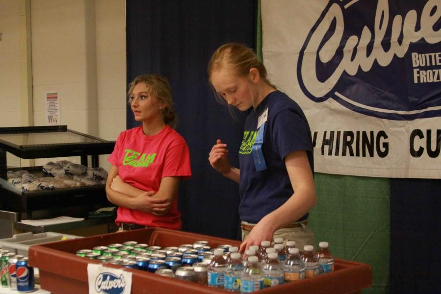 Looking down at the pop and food they are providing, junior Jada Watson helps run the Culver's booth at the community expo over the weekend.