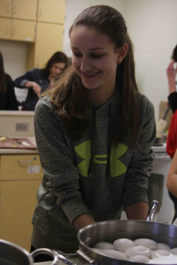 Boiling eggs in the food lab, freshman Anna Janowak dries her hands off.