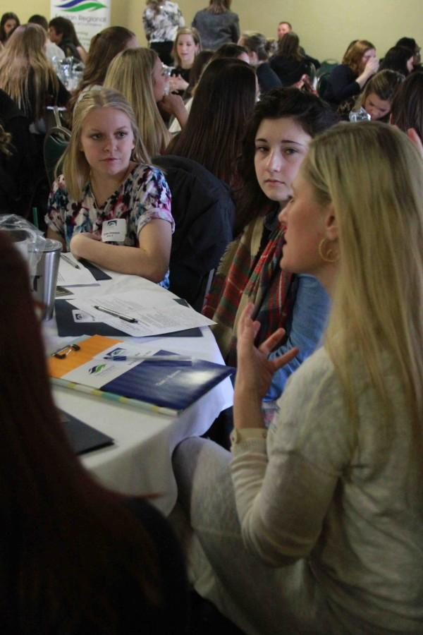 Listening to a speaker at Girls in Business, senior Jessie Maher and junior Jordan Dawson learn more about the business world for women.