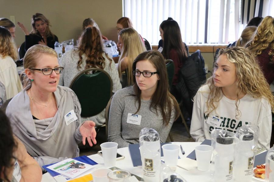 Listening to a speaker, junior Lauryn Bell was on of the girls from Fenton that attended Girls in Business  on March 18.