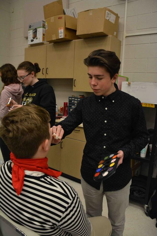 Helping cast members get ready, junior Chase Raymond puts makeup onto a cast member.