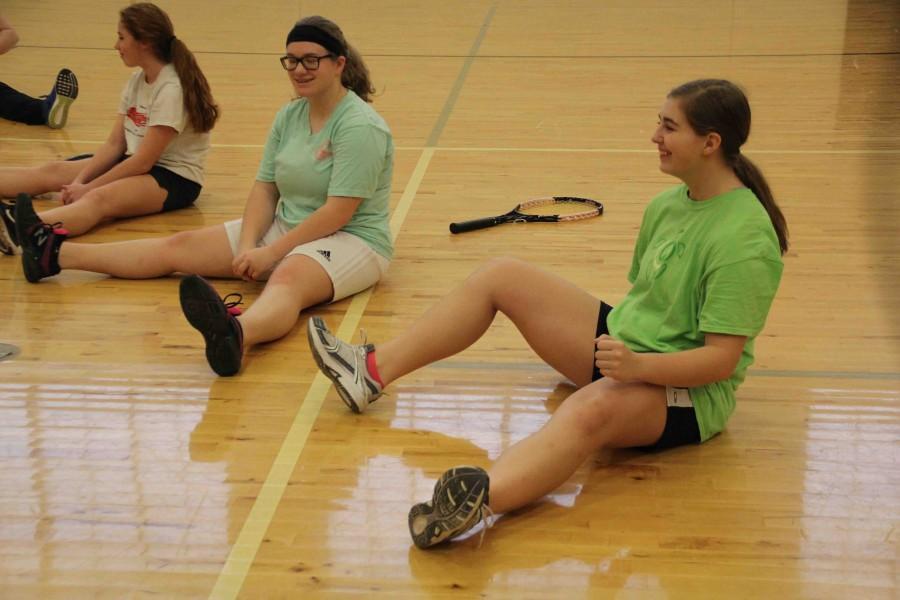 Stretching out before practice, freshman Hannah Ferguson talks with freshman Kara Piwowarczyk.