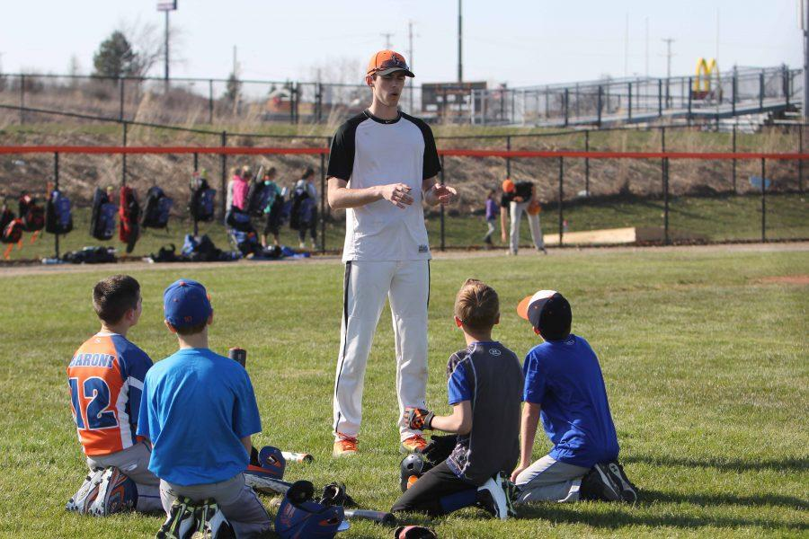 Talking to the kids, senior Taylor Lawrence helps run the baseball clinic for baseball players.