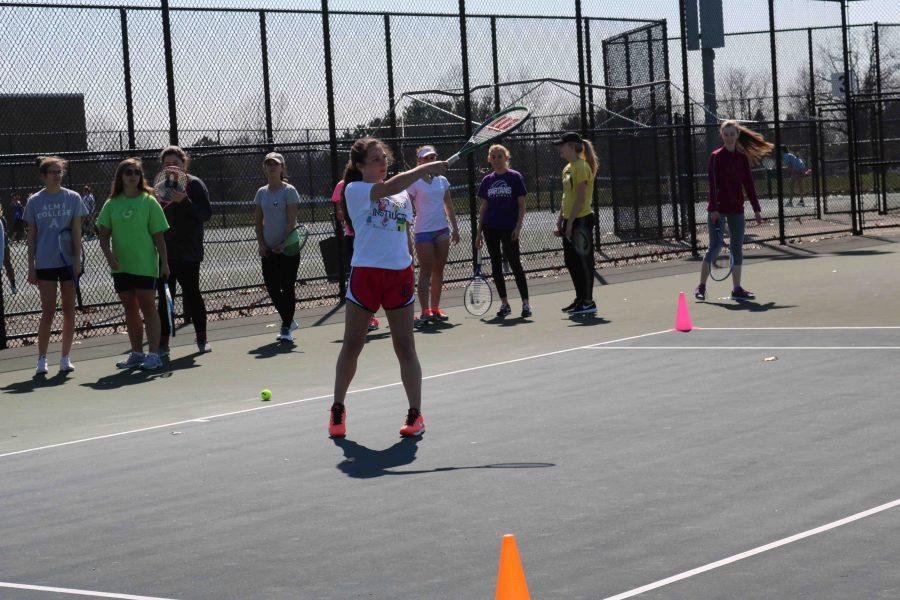 At JV tennis practice, freshman Jamie Elrod hits the tennis ball across the tennis court.